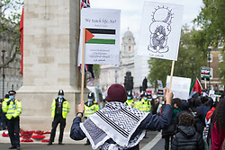 London, UK. 22nd May, 2021. A man passes the Cenotaph holding a placard bearing an image of Handala during the National Demonstration for Palestine. It was organised by pro-Palestinian solidarity groups in protest against Israel's recent attacks on Gaza, its incursions at the Al-Aqsa mosque and its attempts to forcibly displace Palestinian families from the Sheikh Jarrah neighbourhood of East Jerusalem.