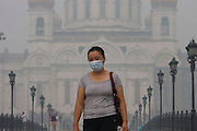 Moscow, Russia, 08/08/2010. .A woman wears a protective mask as she crosses a bridge by the Cathedral of Christ the Saviour in the worst smog so far in the record high temperatures of the continuing heatwave. Peat and forest fires in the countryside surrounding Moscow have resulted in the Russian capital being blanketed in heavy smog.