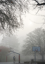 © Licensed to London News Pictures. 01/04/2014. Hammersmith, UK . People exercise on a basketball court. A foggy morning in Ravenscourt Park in Hammersmith West London today April 1st 2014. Photo credit : Stephen Simpson/LNP
