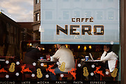 Coffee drinkers sit in the seasonally Xmas decorated window of a branch of Caffe Nero in the weeks before Christmas. Seen from outside, we see two men sit with tie backs to the street while a lady sits sideways working on a laptop computer. The company have displayed a series of reindeer, snowmen and ice crystals along with the coffee varieties that Nero is known for in the UK. Gerry Ford founded Caffè Nero in 1997 and today, Caffè Nero has over 500 stores globally with more than 4,000 employees.