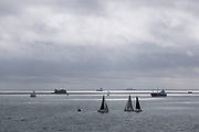 Small yachts and other boats sailing on a calm sea under grey sky off the coast on 26th September 2021 in Plymouth, United Kingdom. The surrounding seas are very popular for people with sail boats and larger yachting crews.