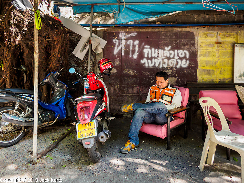 17 DECEMBER 2018 - BANGKOK, THAILAND: A motorcycle taxi waits for customers in a working class neighborhood about one kilometer from Siam Paragon, an exclusive mall in central Bangkok. According to Credit Suisse Global Wealth Databook 2018, which surveyed 40 countries, Thailand has the highest rate of income inequality in the world. In 2016, Thailand was third, behind Russia and India. In 2016, the 1% richest Thais (about 500,000 people) owned 58.0% of the Thailand's wealth. In 2018, they controlled 66.9%. In Russia, those numbers went from 78% in 2016, down to 57.1% in 2018. The Thai government disagreed with the report and said the report didn't take government anti-poverty programs into account and that Thailand was held to an unfair standard because most of the other countries in the report are developed countries in the Organisation for Economic Co-operation and Development.    PHOTO BY JACK KURTZ