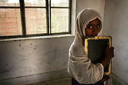 Zahra Khadim, 5, holds a small chalkboard inside the school that Mukhtar Mai created, Meerwala, Pakistan, April 29, 2005. Mai, 33, went against the Pakistani tradition of committing suicide when she brought charges against the men who gang raped her nearly three years ago. With money from the ruling she opened two schools, one for girls, the other for boys, citing that education is the only thing that will stop such acts from happening.