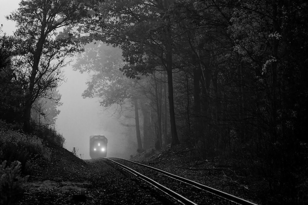 In the woods of upstate New York remain the last active rails of the long abandoned New York, Ontario and Western. Emerging from the fog is the CSX local out of Fulton with two cars to be spotted at industries in Phoenix and Oswego. About 12 active miles remain of the mostly rural and un-needed line that spanned from the New York city area to upstate NY.