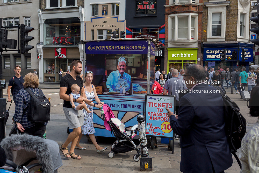 Parents carry their baby past the rear of a newspaper vendor's kiosk outside Liverpool Street mainline station in the City of London - the capital's financial district, on 3rd September 2018, in London England.