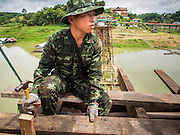 16 SEPTEMBER 2014 - SANGKHLA BURI, KANCHANABURI, THAILAND: A Thai soldier relaxes while working on the repair of the Mon Bridge. The 2800 foot long (850 meters) Saphan Mon (Mon Bridge) spans the Song Kalia River. It is reportedly second longest wooden bridge in the world. The bridge was severely damaged during heavy rainfall in July 2013 when its 230 foot middle section  (70 meters) collapsed during flooding. Officially known as Uttamanusorn Bridge, the bridge has been used by people in Sangkhla Buri (also known as Sangkhlaburi) for 20 years. The bridge was was conceived by Luang Pho Uttama, the late abbot of of Wat Wang Wiwekaram, and was built by hand by Mon refugees from Myanmar (then Burma). The wooden bridge is one of the leading tourist attractions in Kanchanaburi province. The loss of the bridge has hurt the economy of the Mon community opposite Sangkhla Buri. The repair has taken far longer than expected. Thai Prime Minister General Prayuth Chan-ocha ordered an engineer unit of the Royal Thai Army to help the local Mon population repair the bridge. Local people said they hope the bridge is repaired by the end November, which is when the tourist season starts.    PHOTO BY JACK KURTZ
