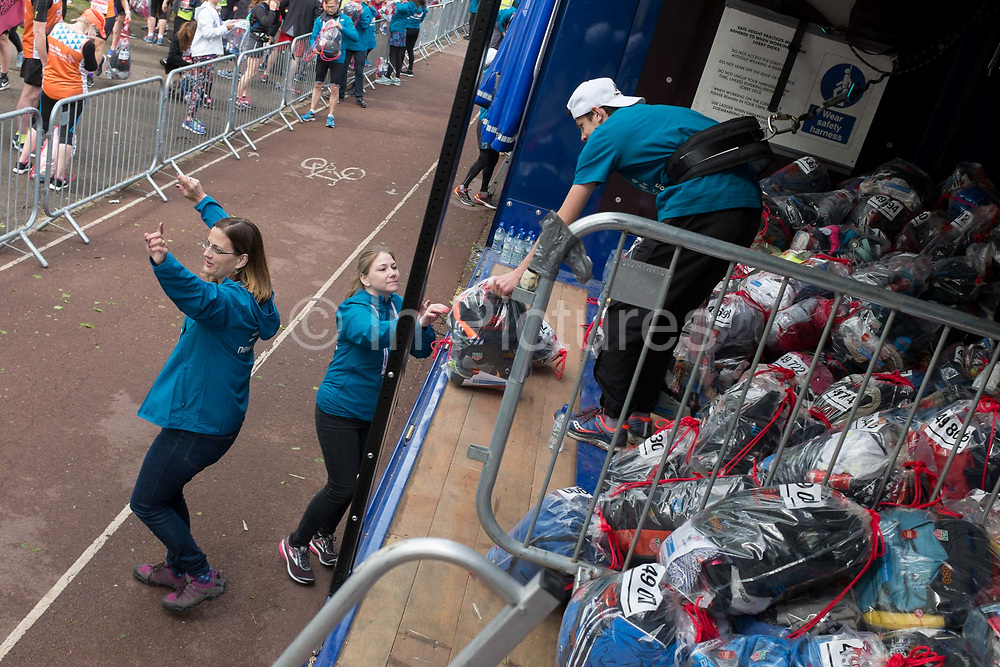 Local London park run volunteers load runners bags into the lorries in Greenwich Park before the start of the 2019 London Marathon, on 28th April 2019, in London, England.