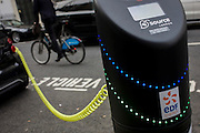 Cyclist passes a parked Smart car recharges electric power at an EDF charging point in central London.