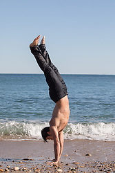 shirtless man doing a handstand at the ocean