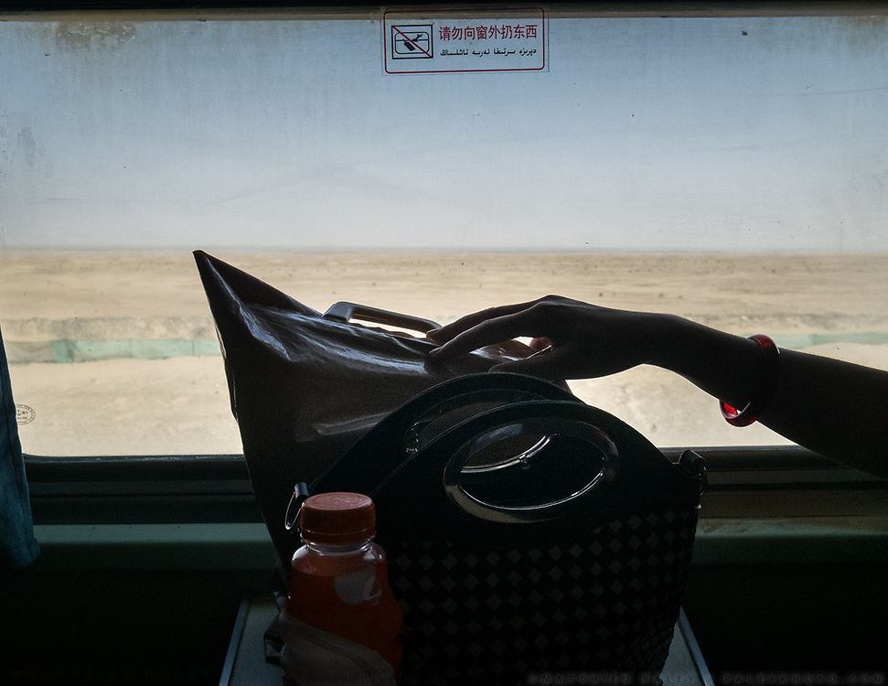 A woman (wearing a jade bracelet, famous in Hotan) reaches out to her food bag in front of the Taklamakan desert. Life inside the train - mostly Muslim Uighur people  ride this train.