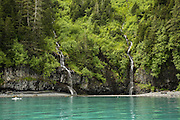 Small cascade in shletered cove with galcier silt in water, Prince William sound, AK
