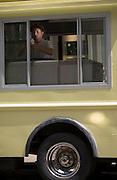 A vendor scoops ice cream for customers in the Van Leeuwen Artisan Ice Cream truck in Soho in New York.