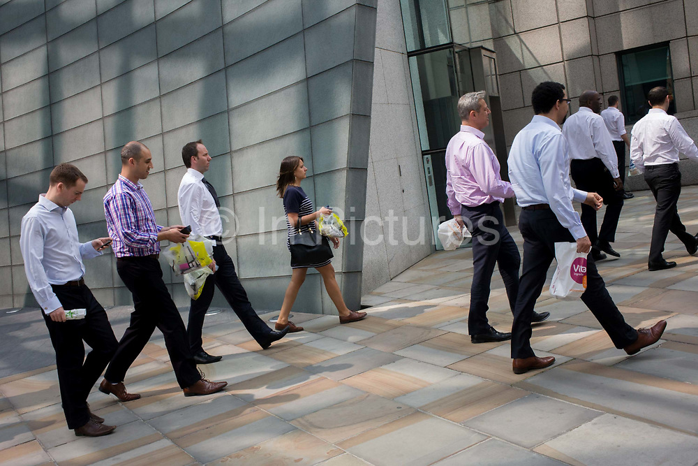 City workers walk along a pedestrian pavement at Broadgate in the City of London. Seemingly walking in step, one female is among many other males, a gender inbalance for the workplace. Broadgate Estate is a large, 32 acre (129,000 m²) office and retail estate in the City of London, owned by British Land and managed by Broadgate Estates. It was originally built by Rosehaugh and was the largest office development in London until the arrival of Canary Wharf in the early 1990s. The City is a major business and financial centre. Throughout the 19th century, the City was perhaps the world's primary business centre, and it continues to be a major meeting point for businesses