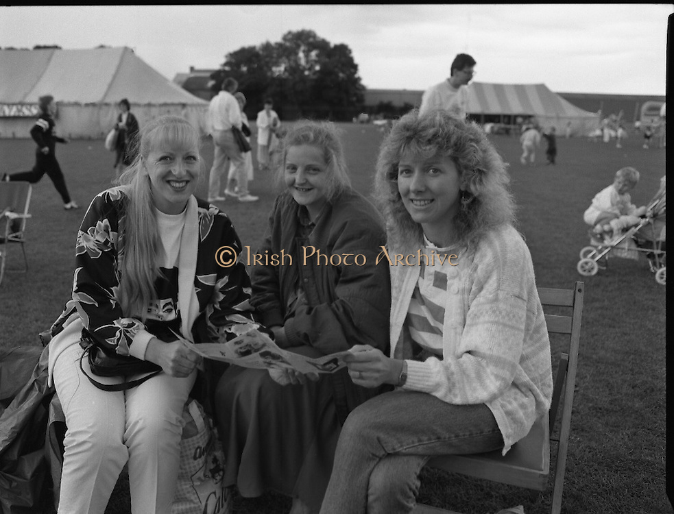 """Guinness Family Day At The Iveagh Gardens. (R83)..1988..02.07.1988..07.02.1988..2nd  July 1988..The family fun day for Guinness employees and their families took place at the Iveagh Gardens today. Top at the bill at the event were """"The Dubliners"""" who treated the crowd to a performance of all their hits. Ireland's penalty hero from Euro 88, Packie Bonner, was on hand to sign autographs for the fans...Three ladies are pictured studying the itinerary for the days events at the family day out."""