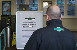 © Licensed to London News Pictures. 14/12/2016. London, UK. A Southern Rail employee looks at a poster announcing the station closure at Selhurst. Hundreds of thousands of rail passengers face a second day of a 3 day rail strike in an escalating dispute over the role of conductors and drivers. Photo credit: Peter Macdiarmid/LNP