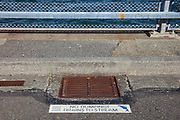 """With the water of Puget Sound in the background, a sign next to a stormwater drain warns people not to dump toxic materials. The sign reads """"No dumping! Drains to stream."""""""