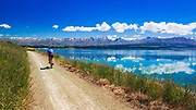 Cyclist riding along the shore of Lake Pukaki under the Southern Alps, Canterbury, South Island, New Zealand