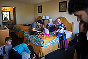 Eight members of the Alsaloum family, Syrian refugees, landed at Tampa International Airport in Tampa, Florida, U.S., January 23, 2017. Four others arrived on January 26. The next day, President Donald Trump signed an executive order halting the entry of Syrian refugees and citizens of six other Muslim-majority nations.<br /> The Alsaloums were more than 6,500 miles from the Syrian village outside Aleppo they used to call home.Along with more than 4.8 million other Syrians, they'd fled the violence that killed some 400,000 of their countrymen.<br /> Now more than five years after leaving everything behind, even the family photo albums, the Alsaloum family settled in at a Days Inn.The chain motel, tucked into the elbow of a freeway exit in the north Tampa sprawl,didn't look like a pit stop on anyone's path to the American dream. But they were safe from war, in a place where their children could grow up with opportunities not possible under Bashar al-Assad's regime.<br /> <br /> Pictured: The Alsaloum family passes the time at a Days Inn in north Tampa, Florida, U.S. shortly after their arrival. Soon after they would transition from the motel to an apartment secured for them by the resettlement agency Coptic Orthodox Charities.