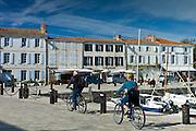 Tourists cycling along the harbour at Quai de Senac in La Flotte, Ile de Re, France