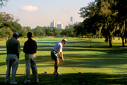 Stock photo of a man with a group teeing off with the downtown Houston skyline on the horizon.