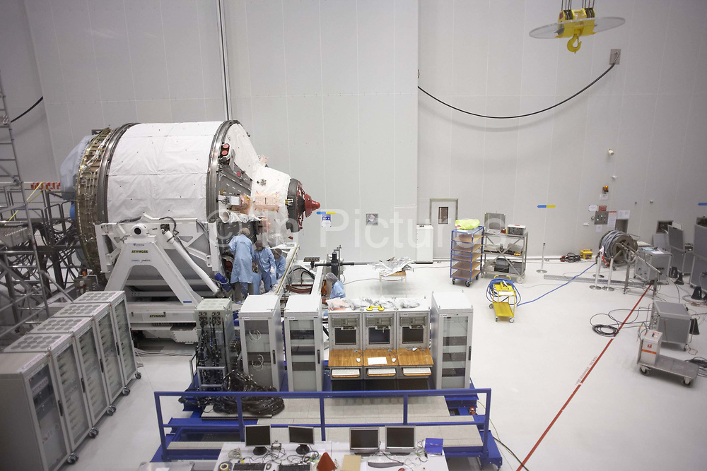 In a sterile clean room, one module section of the European Space Agency's Automated Transfer Vehicle (ATV) called Jules Verne, is under construction by technicians of an integration team at Europe's Spaceport in Kourou, French Guiana. The ATV cargo carrier is the world's largest and most complex orbiting spacecraft and is a new series of autonomous spaceships designed to re-supply the International Space Station with replacement cargo, propellant, water and oxygen to the orbital outpost. Launched in March 2008 and self-destructed with waste during its return to earth's atmosphere that September, it delivered 4.6 tonnes of payload to the ISS, including 1,150 kg of dry cargo, 856 kg of propellant for the Russian Zvezda module, 270 kg of drinking water and 21 kg of oxygen.