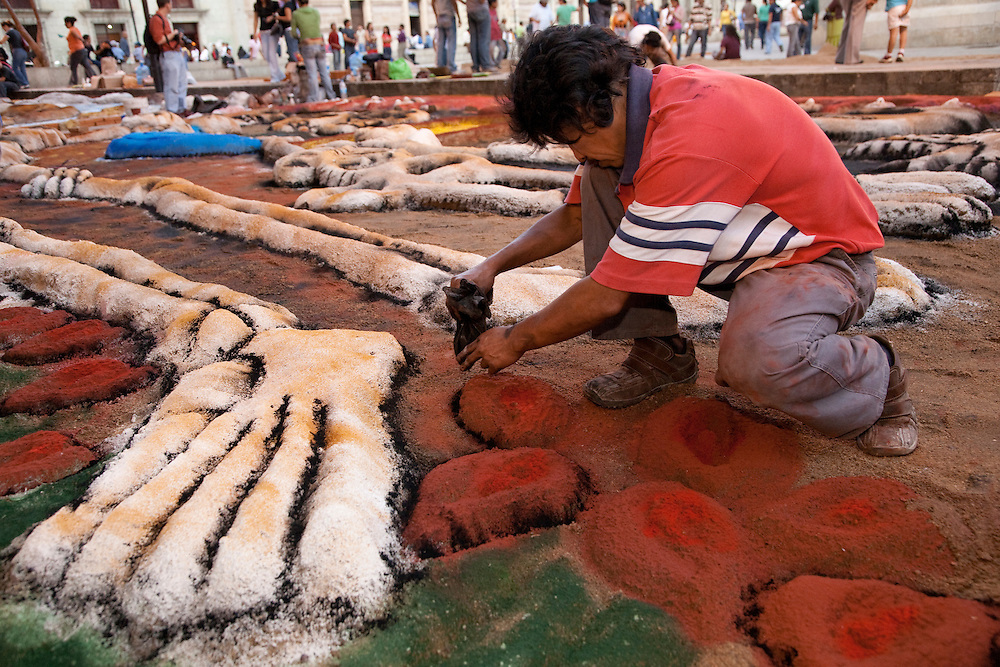 """North America, Mexico, Oaxaca Province, Oaxaca, creation of sand tapestries (Tapetes de Areña) with skeletons in Zocalo plaza.   These  """"carpets""""  are made from sand, dyed sawdust, seeds, flower petals and powdered lime during annual Day of the Dead (Dias de los Muertos) celebration in November"""