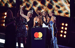 Little Mix's Perrie Edwards, Jesy Nelson, Leigh-Anne Pinnock and Jade Thirlwall collect their award on stage at the Brit Awards at the O2 Arena, London.