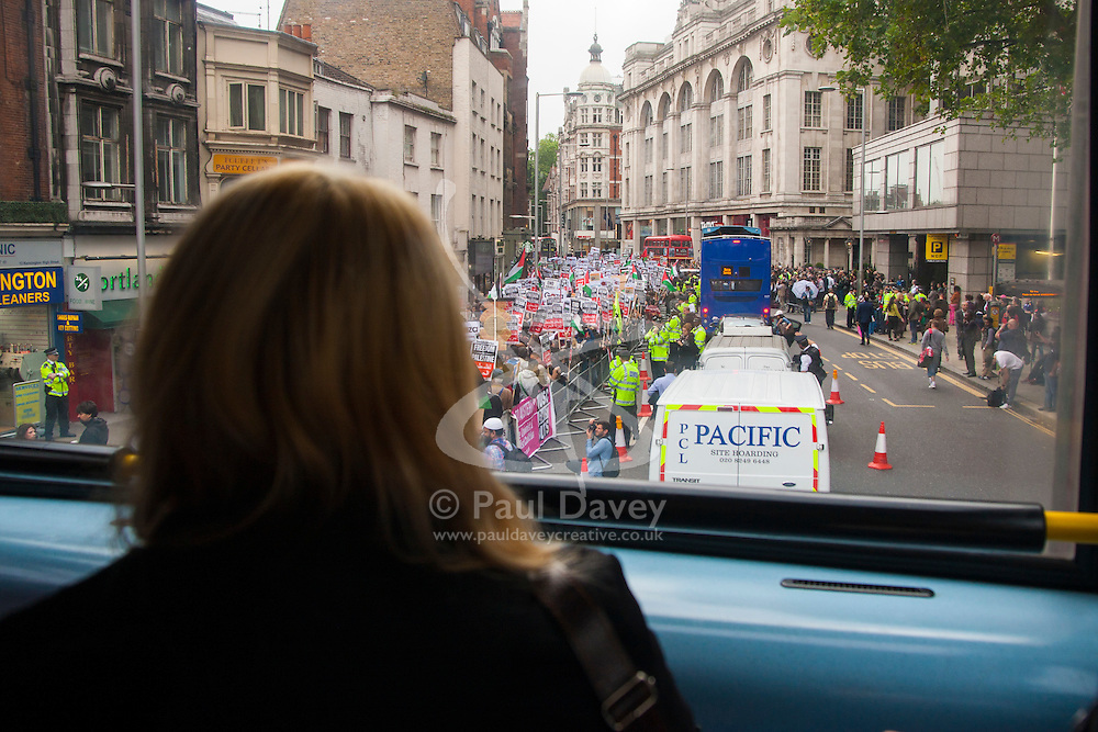 Kesnington, London, July 11th 2014. A stranded bus passenger watches as thousands of Palestinians and their supporters demonstrate against the latest wave of Israeli retaliatory attacks on Palestinian targets and homes, where casualties are steadily mounting.