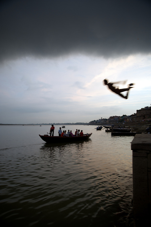 As dusk falls along the Ganges River in Varanasi, India, a young man suddenly appears as he leaps into the river.