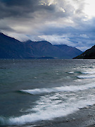 View of sunset and waves from the shore of Lake Wakatipu on a windy evening, just north of Queenstown, Otago, New Zealand