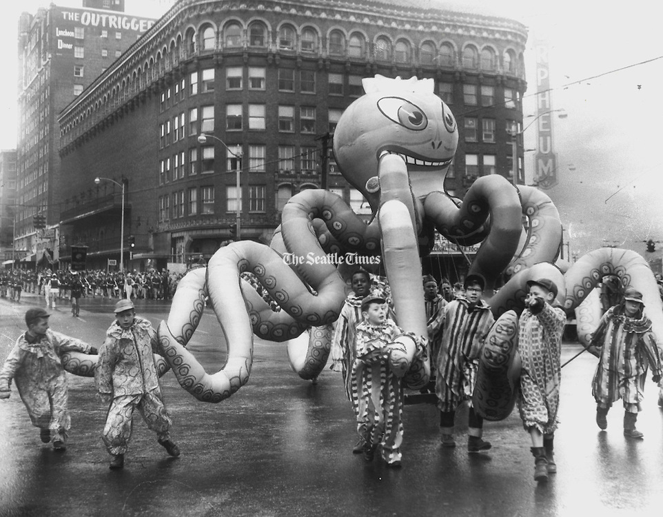 This blue-eyed octopus that wiggled ten tentacles menacingly was one of many new balloons in the seventh annual Santa Claus Parade. Glistening in the sun, the rubbery denizen of the deep was hauled by a team of Boy Scouts. It typified the parade's salty Christmas theme. (Harold Smith / The Seattle Times, 1955).