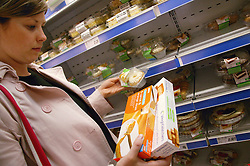 Woman checking fat content on a packet of cakes,