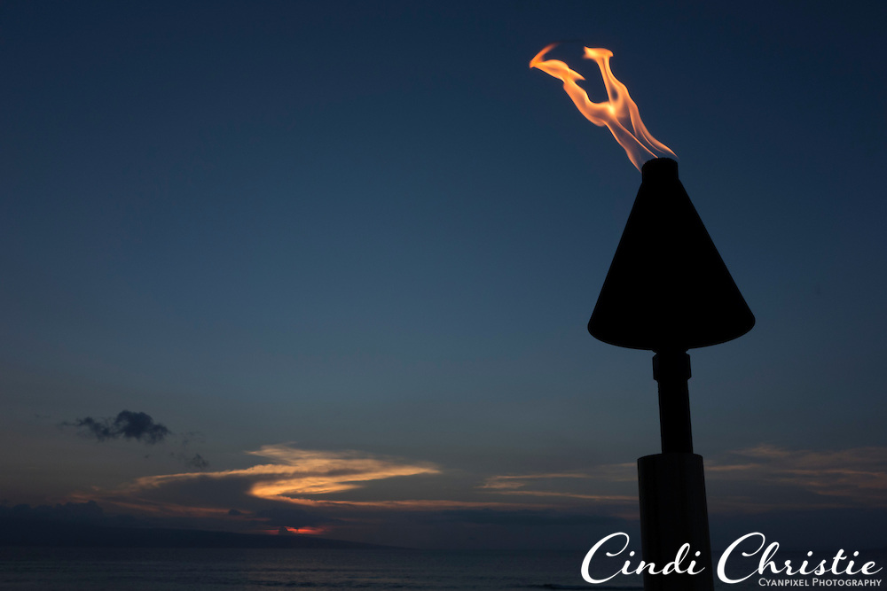 A torch burns as the sun sets beyond the island of Lanai as seen from Ka'anapali Beach in Lahaina, Hawaii, on Sunday, Oct. 27, 2013. (© 2013 Cindi Christie/Cyanpixel)