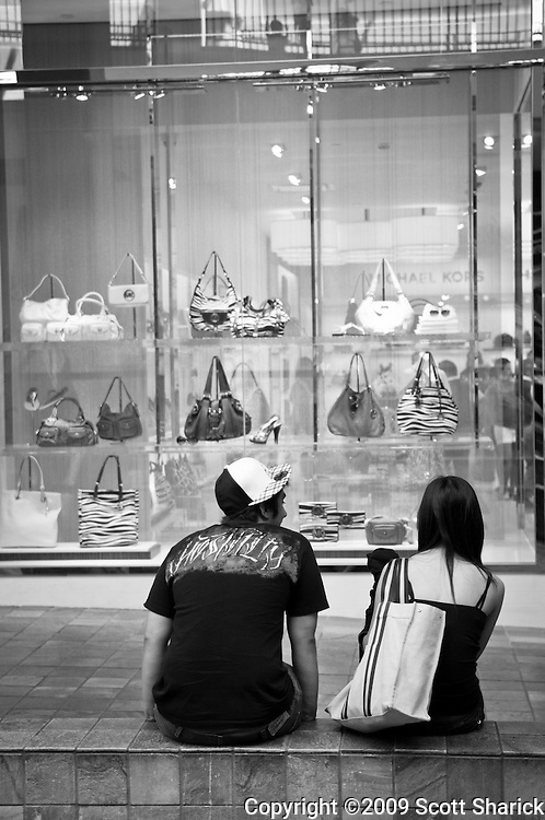 A young couple taking a rest from shopping at the mall.