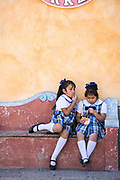 Young school girls play in the town square in the beautiful colonial village of Bernal, Queretaro, Mexico. Bernal is a quaint colonial town known for the Pena de Bernal, a giant monolith which dominates the tiny village is the third highest on the planet.