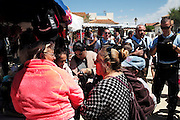 """The Gitan market place with a family of gitan gypsies near the Town Hall. French police patrol the seaside town of Saintes Maries de la Mer during the pilgrimage. With rising of the french 'Front National', which the Mayor belongs too, and racism and prejudice the gypsies feel less and less welcome these days to their own festival<br /><br />""""Le Pelerinage des Gitans""""; the French gypsy pilgrimage of Saintes Maries de la Mer, Camargue, France<br /><br />Sainte Sara is an uncannonized saint, who legend says looked after the Christian Saints Marie Jacobe and Marie Salome, cousins of Mary Magdalene, who arrived, it is said, on the shores of the Camargue in a rudderless boat. Saint Sara is the patron saint of gypsies who come from far and wide to see her. There are even paintings of Sara as 'Kali' the black saint in Eastern Europe. Sara may have been the priestess of 'Ra' the sun-god or even servant girl to the Christian saints. No-one really knows.<br /><br />For a few weeks of the year, Roma, Gitan and Manouche gypsies come from all over Europe in May, camping in caravans around Saintes Maries de la Mer. It is a festive time where they play music, dance, party and christen their children. They all go to see Saint Sara in the crypt, kissing or touching her forehead. Many put robes on her shoulders, making her fat for the procession. In the main Gypsy procession of the 24th May, Saint Sara is allowed to leave her crypt, beneath the church, and is carried from the church to the shores of the mediterranean and back again. One day a year she is free from her prison. Hundred's of years ago the Gypsies used not even to be allowed into the church, only into the crypt like Sara...<br /><br />Roma gypsies still suffer oppressive prejudice and racism and are one of the ethnic groups the most persecuted and marginalised across Europe. The festival is one of the times where they celebrate with people of all races, their faith and traditions"""