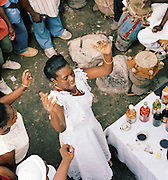 A local woman worshipping at a Haitain Voodoo ceremony on the streets of Port-Au-Prince, Haiti