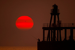 © Licensed to London News Pictures. 22/07/2021. Whitby UK. A fisherman casts off from the end of Whitby pier this morning as the sun rises in Yorkshire on another hot day in the UK. Photo credit: Andrew McCaren/LNP