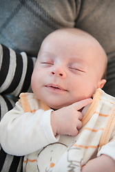 Baby boy sleeping safe in arms of his parents, close up