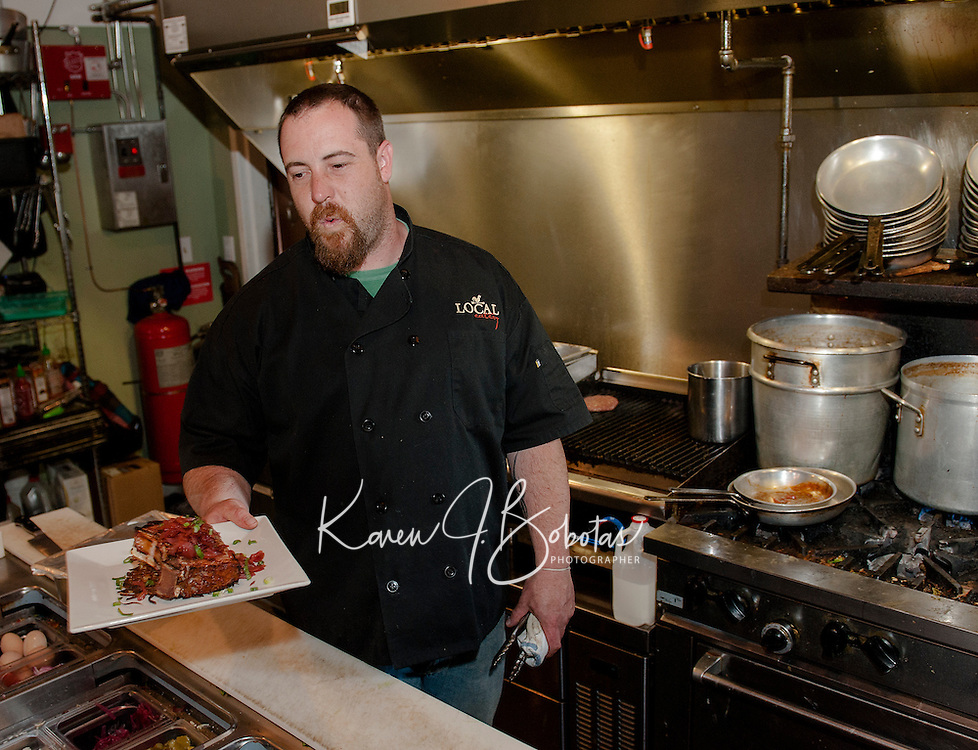 """Chef Kevin Halligan prepares a house-raised smoked pork chop with potato latkes, parsnip apple puree with red onion jam for """"Restaurant Week"""" at The Local Eatery on Tuesday evening.   (Karen Bobotas/for the Laconia Daily Sun)"""