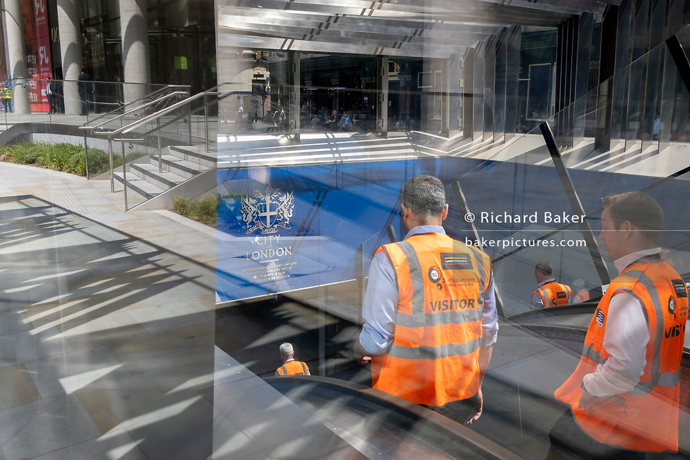 Site visitors descend escalators at the closed station entrance of Crossrail's Elizabeth Line at Liverpool Street in the City of London, the capital's financial district, on 8th June 2021, in London, England. Crossrail has been delayed until 2022 and will need an extra £1.1bn to complete. Running through the heart of London, it will now open more than four years late and cost almost £4bn more than originally planned. The giant infrastructure scheme had originally planned to cost £14.8bn, with services planned to start operating in December 2018.