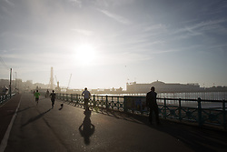 © Licensed to London News Pictures . 24/09/2013 . Brighton , UK . Stunning bright sun bursts through morning mist on the seafront in Brighton this morning (Tuesday 24th September 2013) casting long shadows from commuters . Photo credit : Joel Goodman/LNP
