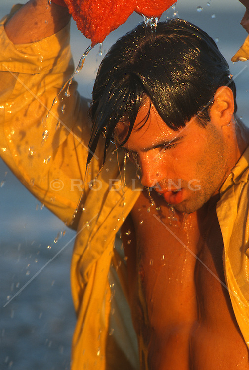Man with a towel soaking himself with water during sunset