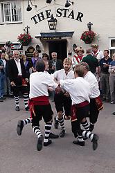 Group of sword dancers performing dance outside village pub,