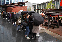© Licensed to London News Pictures. 15/05/2021. Manchester ,UK. Members of the public brave the rain as they queue to enter a beer garden in Manchester city centre. Photo credit: Ioannis Alexopoulos/LNP