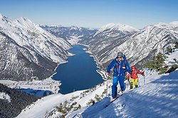 Skiers walking on snow covered mountain