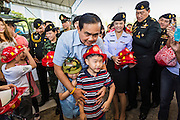 "11 JANUARY 2014 - BANGKOK, THAILAND: General PRAYUTH CHAN-OCHA, Commender in Chief of the Thai Royal Army, give children toy helmets during a Children's Day fair in Bangkok. The Royal Thai Army hosted a ""Children's Day"" event at the 2nd Cavalry King's Guard Division base in Bangkok. Children had an opportunity to look at military weapons, climb around on tanks, artillery pieces and helicopters and look at battlefield medical facilities. The Children's Day fair comes amidst political strife and concerns of a possible coup in Thailand. Gen Prayuth has issued mixed signal on a coup at one point saying there wouldn't be one, and later saying he wouldn't talk about a possible coup. Earlier in the week, the Thai army announced that movements of armored vehicles through Bangkok were not in preparation of a coup, but were moving equipment into position for Children's Day.      PHOTO BY JACK KURTZ"