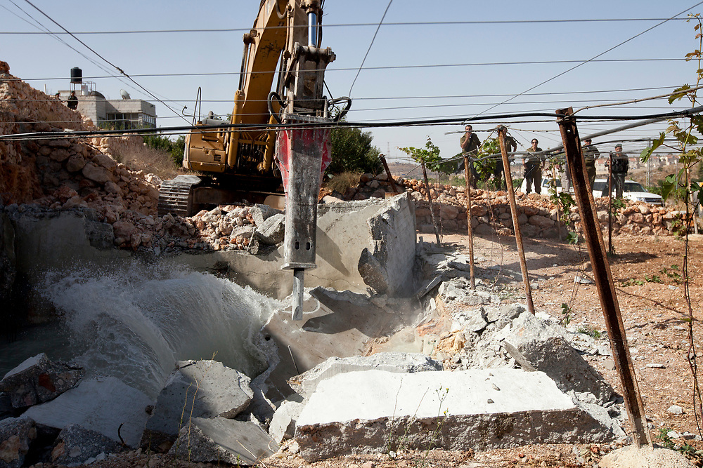 Israeli border police officers stand guard as construction vehicles destroy a man-made reservoir on a Palestinian farm near the West Bank city of Hebron on 14 July 2010.