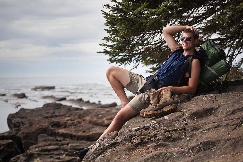 Henry relaxes on the rocky shoreline at Dare Beach, West Coast Trail, British Columbia, Canada.