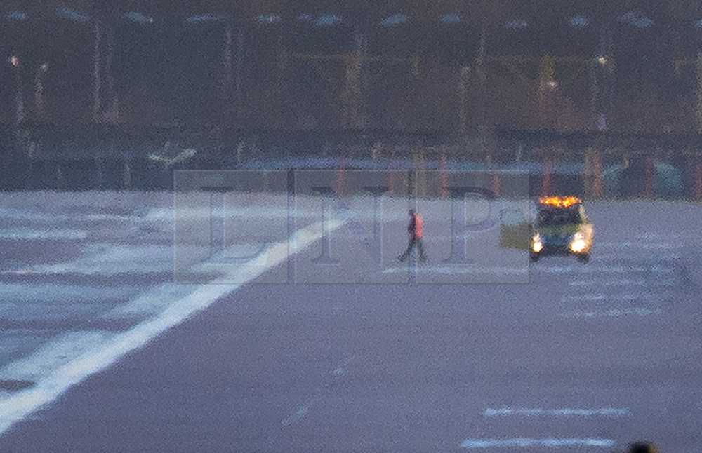 © Licensed to London News Pictures. 20/12/2018. London, UK.A worker checks the runway surface at Gatwick airport. Flights have been cancelled and thousands of passengers have been delayed after the airport closed due to two drones being spotted nearby. Photo credit: Peter Macdiarmid/LNP